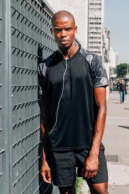 Porträt eines jungen männlichen athleten, der auf tor mit kopfhörern in seinen ohren sich lehnt Kostenlose Fotos