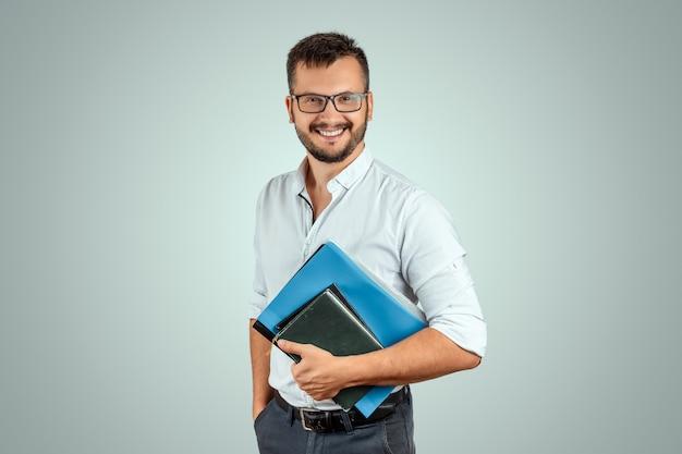 Porträt eines jungen männlichen lehrers auf einem hellen hintergrund Premium Fotos