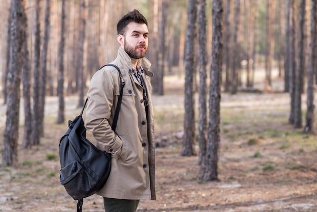 Porträt eines jungen männlichen reisenden, der rucksack auf seiner schulter im wald hält Kostenlose Fotos