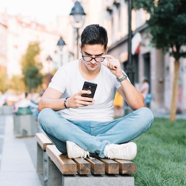 Porträt eines jungen mannes, der auf der bank betrachtet smartphoneschirm sitzt Kostenlose Fotos