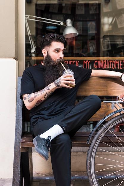 Porträt eines jungen mannes, der auf der bank trinkt die erneuernde köstliche schokoladenmilch sitzt Kostenlose Fotos