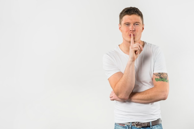 Porträt eines jungen mannes, der das gestikulieren für ruhe mit dem finger macht Kostenlose Fotos