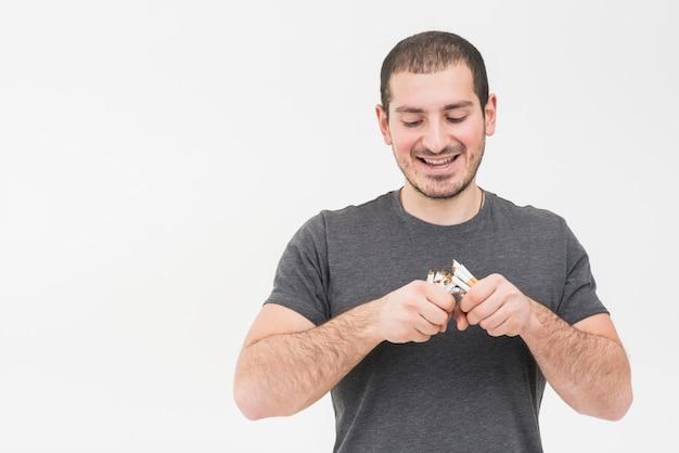 Porträt eines jungen mannes, der den haufen von den zigaretten lokalisiert auf weißem hintergrund bricht Kostenlose Fotos