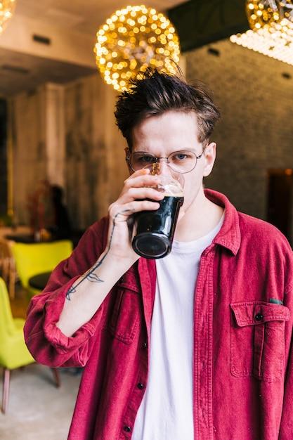 Porträt eines jungen mannes, der die kamera trinkt die biergläser betrachtet Kostenlose Fotos