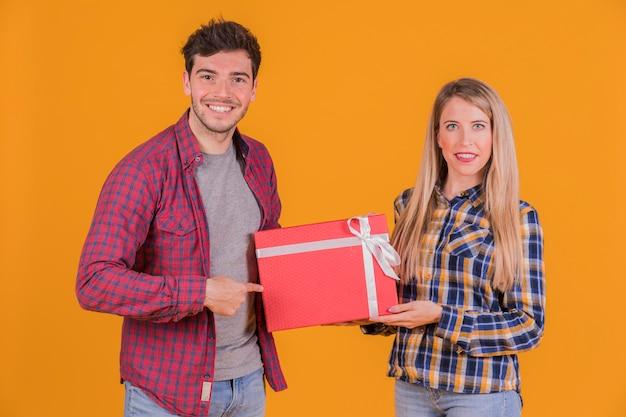Porträt eines jungen mannes, der finger auf geschenkboxgriff von seiner freundin gegen einen orange hintergrund zeigt Kostenlose Fotos