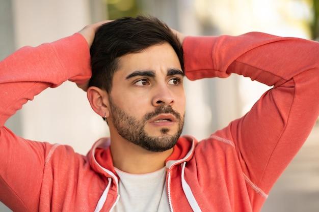 Porträt eines jungen mannes, der gestresst und besorgt über etwas ist, während er draußen steht. stadtkonzept. Kostenlose Fotos