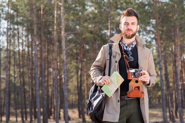 Porträt eines jungen mannes, der in der waldholdingkarten- und -weinlesekamera steht Kostenlose Fotos