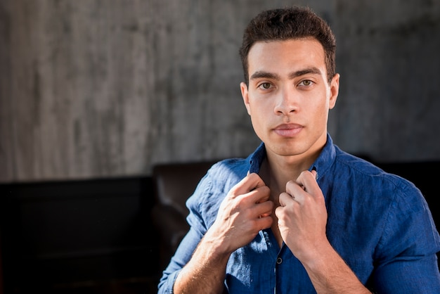 Porträt eines jungen mannes, der kragen seines hemdes betrachtet kamera hält Kostenlose Fotos