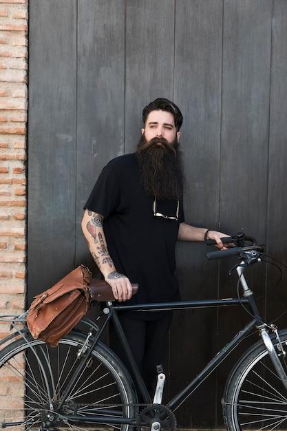 Porträt eines jungen mannes, der mit fahrrad vor geschlossener schwarzer tür steht Kostenlose Fotos