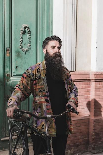Porträt eines jungen mannes, der mit seinem fahrrad steht Kostenlose Fotos