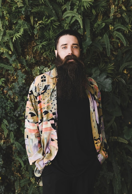 Porträt eines jungen mannes mit dem langen bart, der kamera betrachtet Kostenlose Fotos