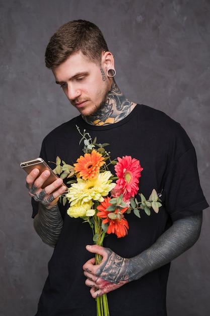 Porträt eines jungen mannes mit durchbohrten ohren und nase, die in der hand blume unter verwendung des smartphone hält Kostenlose Fotos
