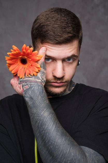 Porträt eines jungen mannes mit tätowierung in seiner hand, die in der hand gerberablume hält Kostenlose Fotos
