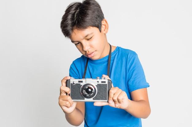 Porträt eines jungen mit der kamera lokalisiert auf weiß Premium Fotos