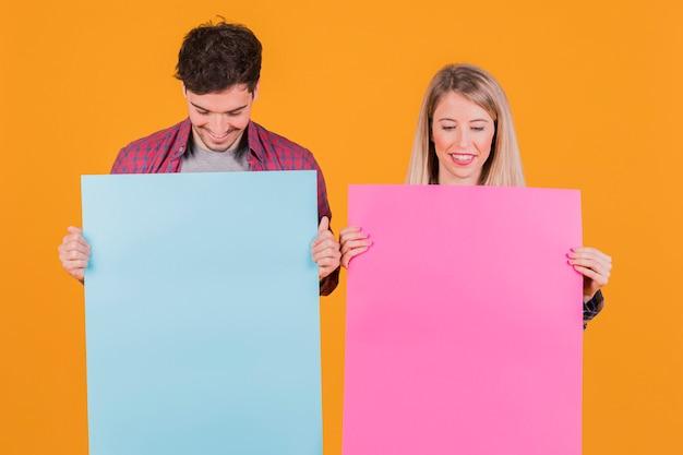 Porträt eines jungen paares, das blaues und rosa plakat gegen einen orange hintergrund betrachtet Kostenlose Fotos