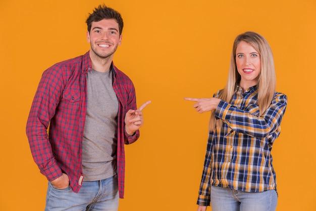 Porträt eines jungen paares, das miteinander ihre finger gegen einen orange hintergrund zeigt Kostenlose Fotos