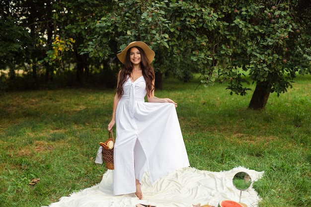 Porträt eines jungen schönen mädchens mit sogar weißen zähnen, einem schönen lächeln in einem strohhut und einem langen weißen kleid machen ein picknick im garten. Premium Fotos