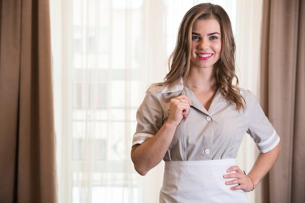Porträt eines jungen stubenmädchens, das ihren kragen steht im hotelzimmer hält Kostenlose Fotos