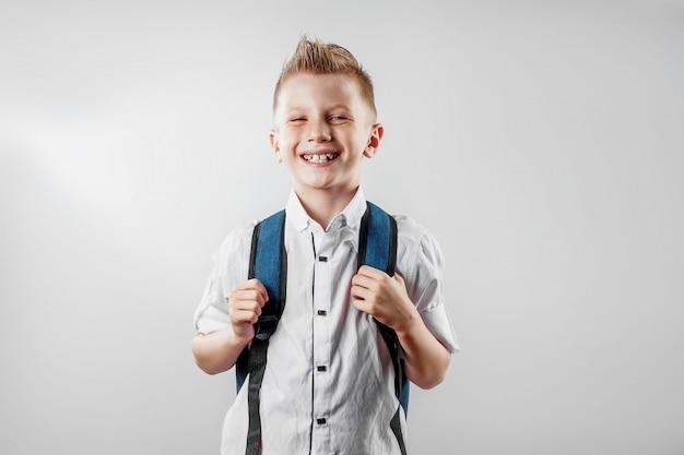Porträt eines jungen von einer grundschule auf einem hellen hintergrund Premium Fotos