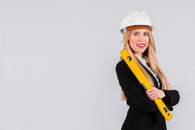 Porträt eines jungen weiblichen architekten, der in der hand das machthaber betrachtet kamera hält Kostenlose Fotos