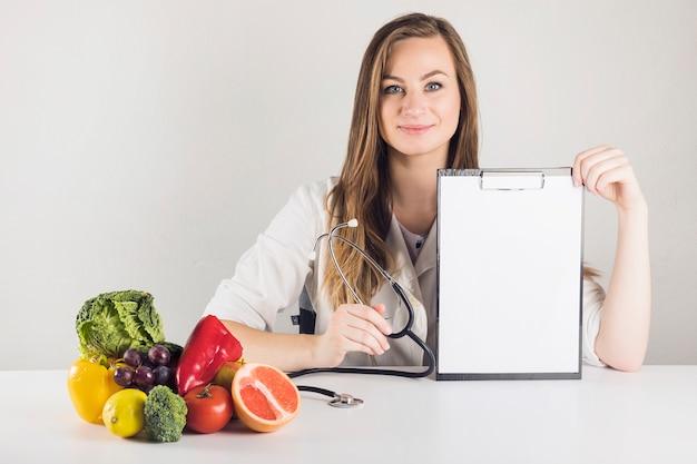 Porträt eines jungen weiblichen diätmachers, der leeres klemmbrett in der klinik hält Kostenlose Fotos