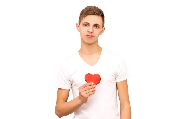 Porträt eines kerls in einem weißen t-shirt, das ein herz, isolat hält Premium Fotos