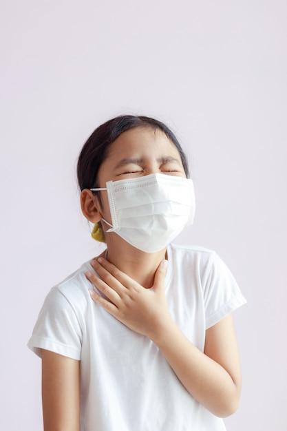 Porträt eines kleinen asiatischen mädchens, das ihren hals mit halsschmerzen berührt Premium Fotos