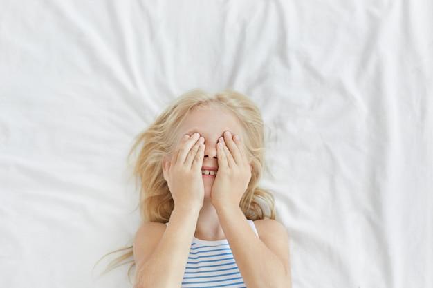 Porträt eines kleinen entzückenden mädchens mit hellem haar, das ihre augen mit händen bedeckt, während es spaß hat und sich vor jemandem versteckt, lachend, auf weißer bettwäsche liegend. sorgloses kind, das morgens aufwacht Kostenlose Fotos