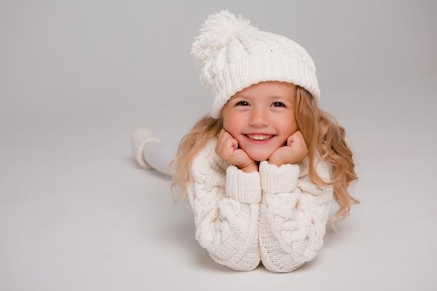 Porträt eines kleinen gelockten mädchens in einem gestrickten weißen winterhut Premium Fotos