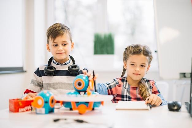 Porträt eines kleinen jungen, der das mädchen spielt mit roboterspielzeug betrachtet Kostenlose Fotos
