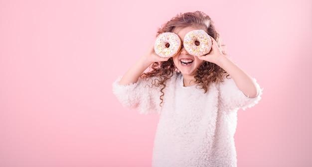 Porträt eines kleinen lächelnden mädchens mit donuts Kostenlose Fotos