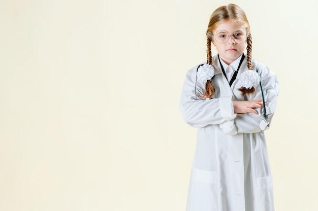 Porträt eines kleinen mädchens in einem mantel weißen doktors mit gläsern, dokumenten und einem stethoskop, das die kamera betrachtet und lächelt Premium Fotos