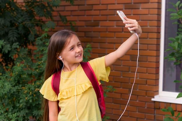 Porträt eines kleinen schönen mädchens, das einen handy verwendet und ein selfie nimmt Premium Fotos