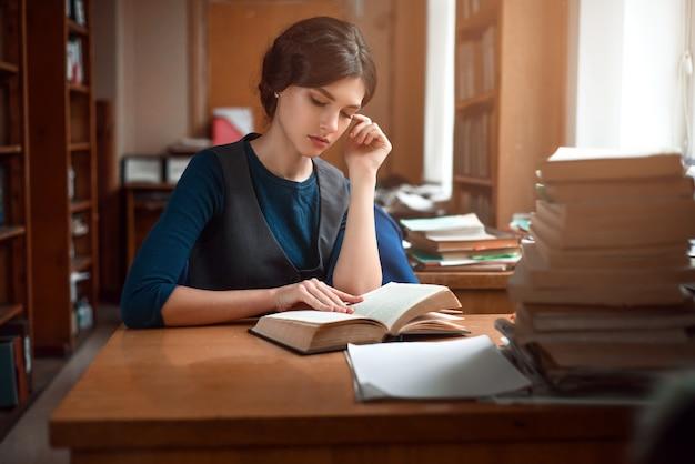 Porträt eines klugen studenten in der universitätsbibliothek. Premium Fotos