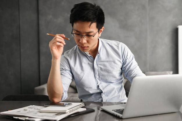 Porträt eines konzentrierten jungen asiatischen mannes Premium Fotos