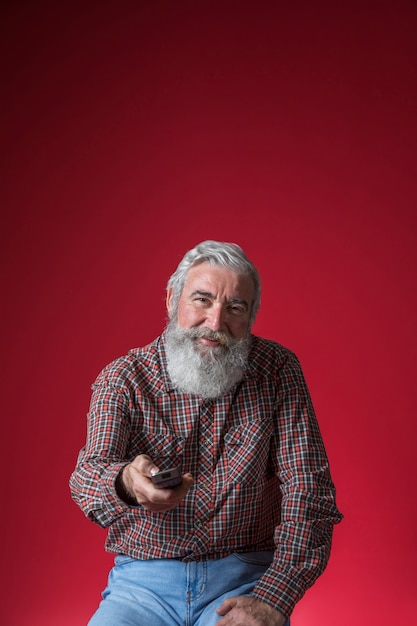 Porträt eines lächelnden älteren mannes, der den kanal mit fernbedienung ändert Kostenlose Fotos