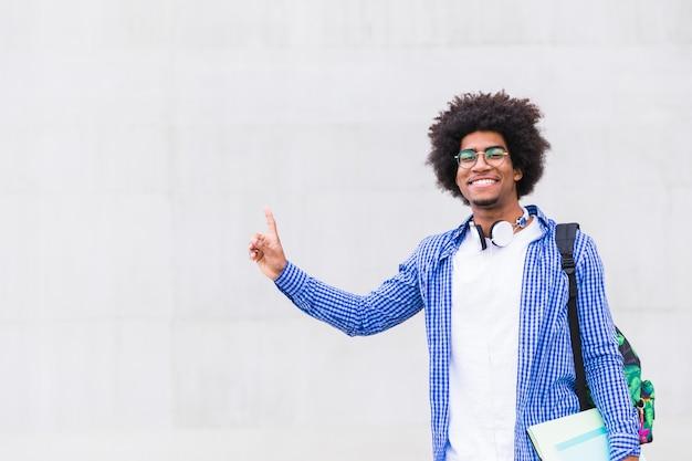 Porträt eines lächelnden afrikanischen mannes, der in der hand bücher hält, die seinen finger gegen graue wand zeigen Kostenlose Fotos