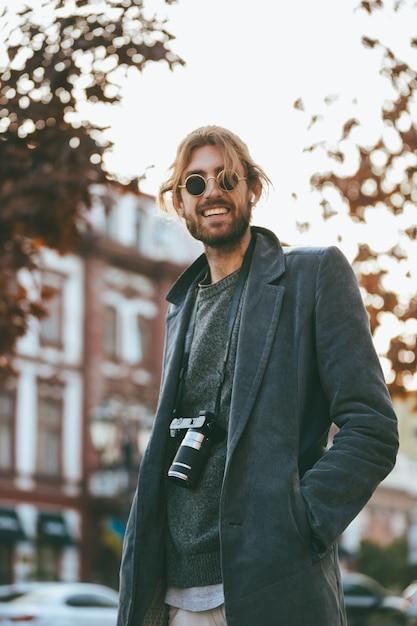 Porträt eines lächelnden bärtigen mannes mit kamera Kostenlose Fotos