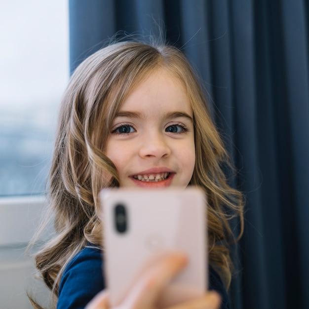 Porträt eines lächelnden blonden mädchens, das selbstporträt am handy nimmt Kostenlose Fotos