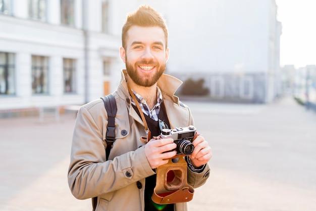 Porträt eines lächelnden hübschen jungen mannes, der in der stadt in der hand hält kamera steht Kostenlose Fotos