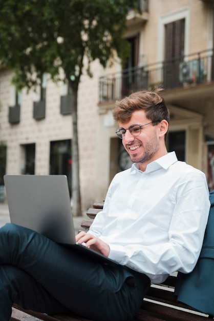 Porträt eines lächelnden jungen geschäftsmannes unter verwendung des laptops Kostenlose Fotos