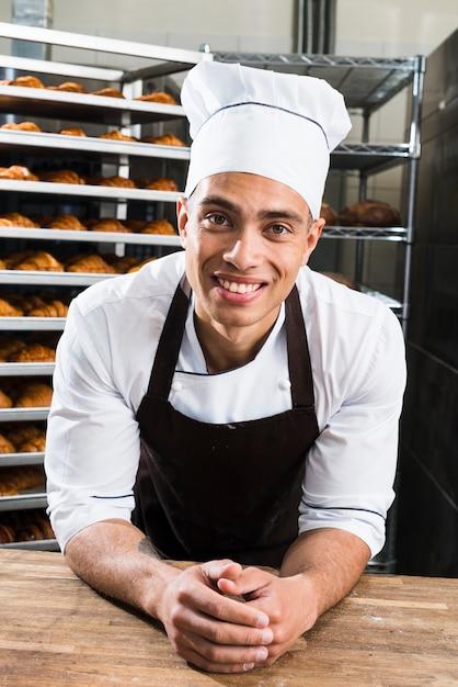 Porträt eines lächelnden jungen männlichen bäckers in der uniform, die auf tabelle in der bäckerei sich lehnt Kostenlose Fotos