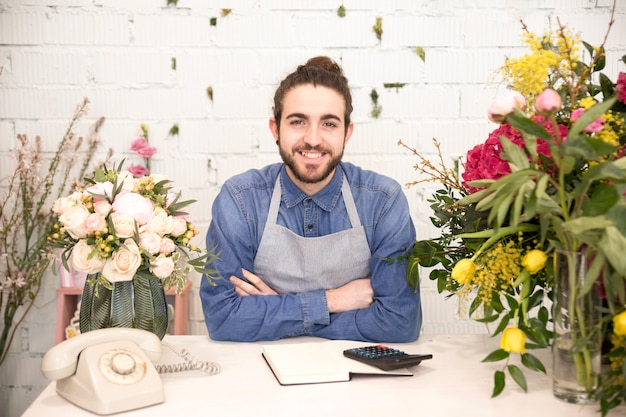 Porträt eines lächelnden jungen männlichen floristen mit den bunten blumen im shop Kostenlose Fotos