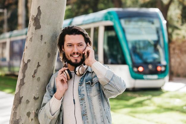 Porträt eines lächelnden jungen mannes, der am handy gegen unscharfen bus spricht Kostenlose Fotos