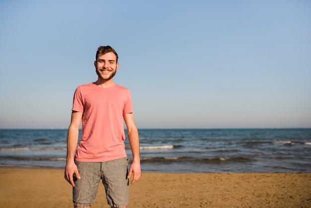 Porträt eines lächelnden jungen mannes, der auf dem strand gegen blauen himmel steht Kostenlose Fotos