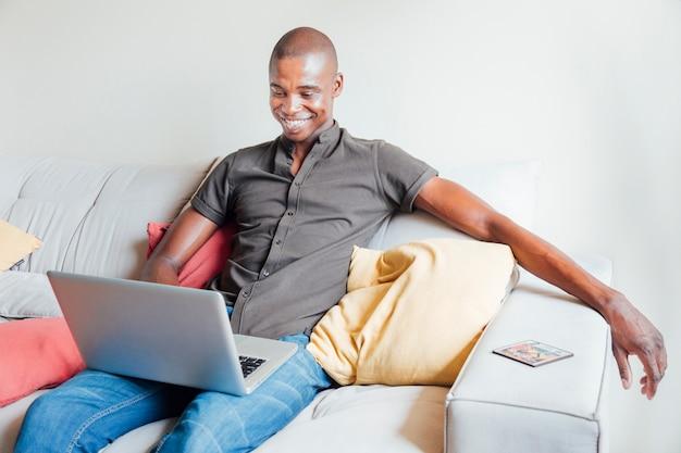 Porträt eines lächelnden jungen mannes, der auf sofa unter verwendung des laptops sitzt Kostenlose Fotos