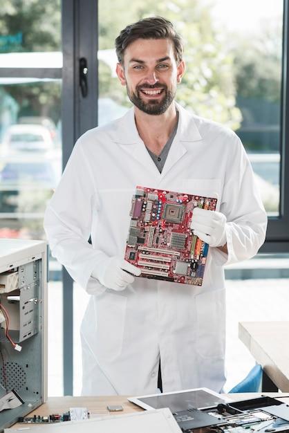 Porträt eines lächelnden jungen mannes, der computermotherboard hält Kostenlose Fotos