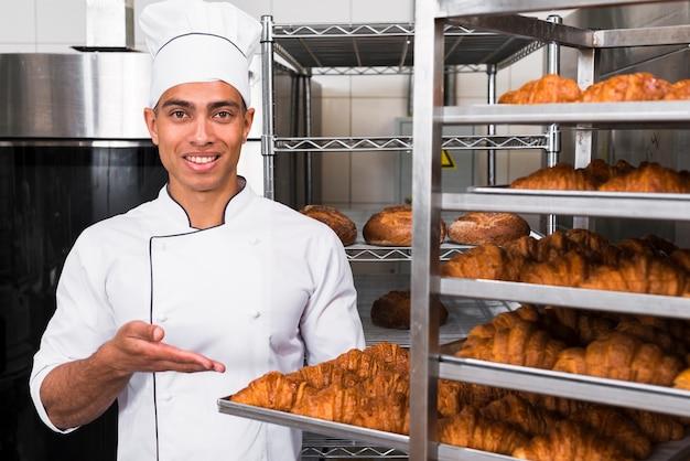 Porträt eines lächelnden jungen mannes, der frisch gebackenes hörnchen auf behälter im regal zeigt Kostenlose Fotos