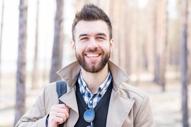 Porträt eines lächelnden jungen mannes, der kamera betrachtet Kostenlose Fotos