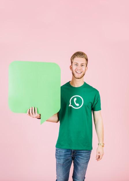 Porträt eines lächelnden jungen mannes, der leere grüne spracheblase hält Kostenlose Fotos